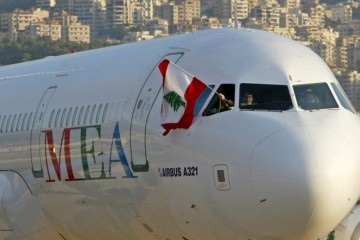 A member of a flight crew waves a Lebanese flag from a Middle East Airlines plane after landing at Beirut's international airport