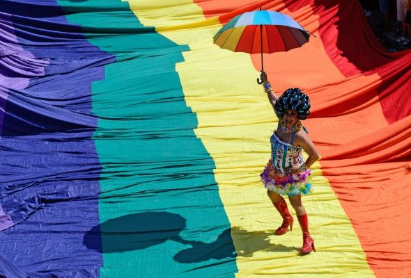459080120-reveller-poses-on-a-giant-rainbow-flag-during-the.jpg.CROP.promo-mediumlarge
